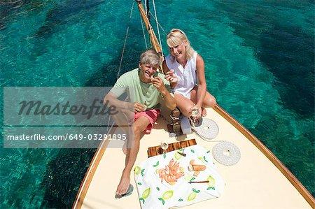 A senior couple picnic while sailing