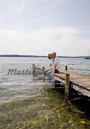 senior man sitting on pier at lake