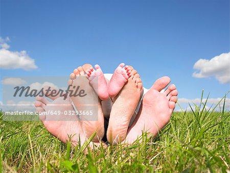 feet of family lying in field