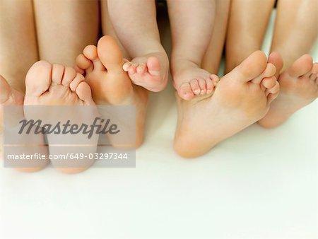 A row of bare feet on a white sheet