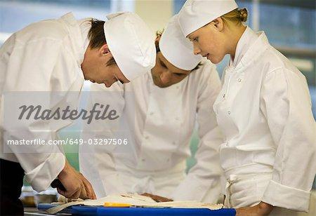 Three chefs filleting a fish