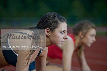 2 female athletes in starting blocks