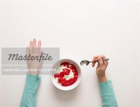 Hands by a bowl of desert