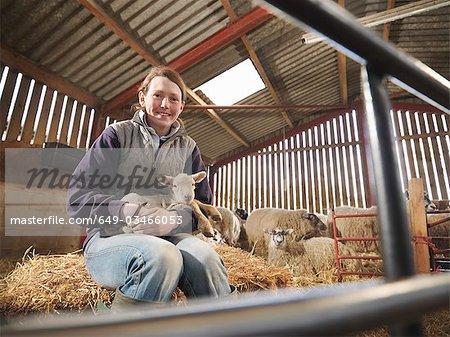Female Farmer Holding Young Lamb