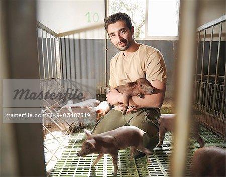 Man in pig pen holding piglet