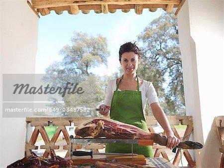 Woman holding knife and ham leg