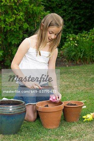 Young girl planting piggy banks