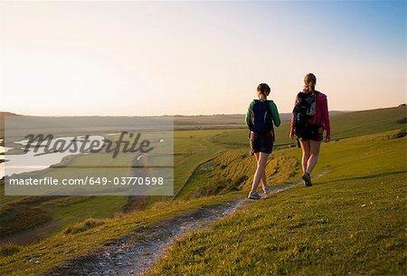 Hikers walk towards sunset