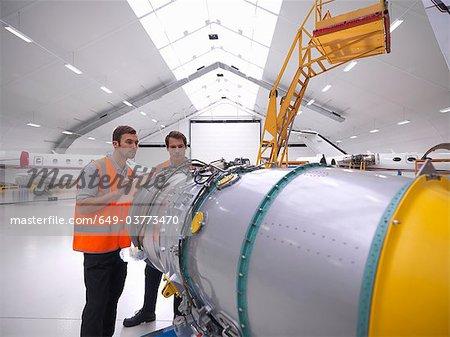 Engineers inspect jet engine