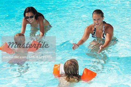Women teaching to kids how to swim