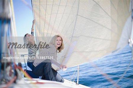 Women adjusting sail on boat
