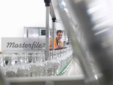 Factory worker examining bottles