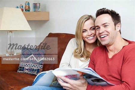 Couple reading magazine together on sofa
