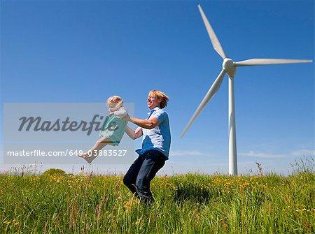 Man in daughter in field by wind turbine