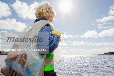 Boy hauling bag of trash on beach
