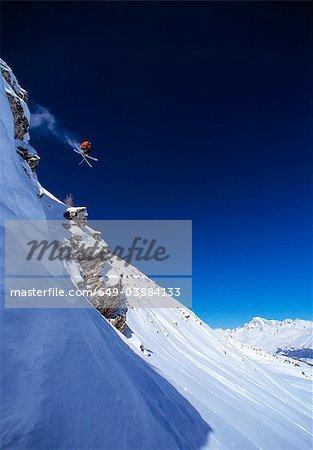 Skier making jump on mountainside