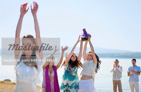 Women catching bride's bouquet