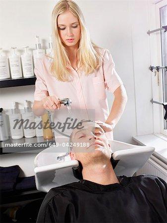 Hairdresser washing man's hair