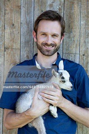 Man holding kid goat outdoors