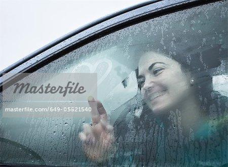 Teenage girl drawing on wet car window