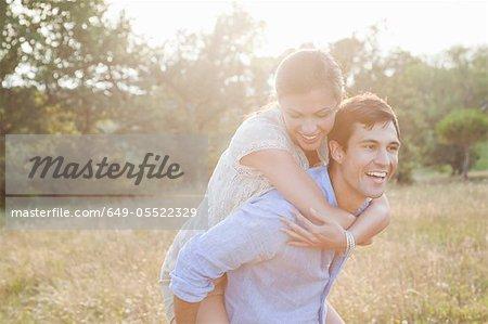 Man carrying girlfriend piggyback