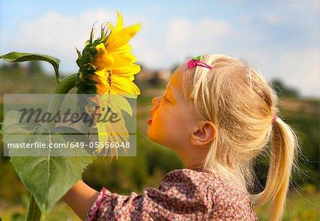 Girl smelling sunflower outdoors