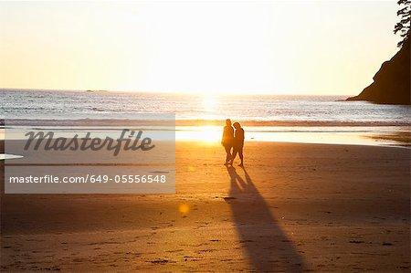 Couple walking on beach on sunset