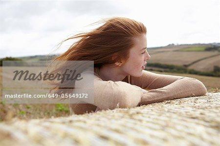 Teenage girl resting on haybale