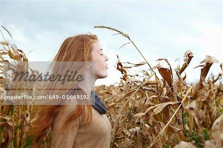 Teenage girl walking in cornfield