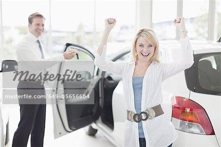 Woman cheering in car dealership