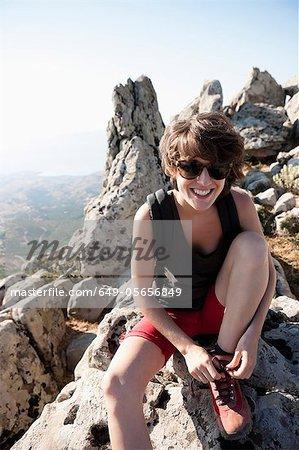 Hiker tying her shoe on rocks