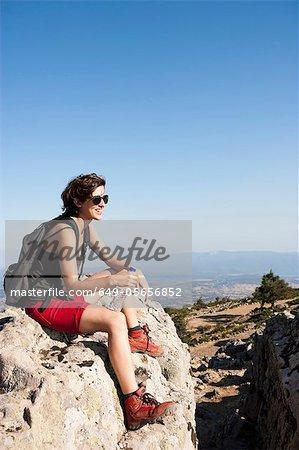 Hiker resting on rocks on hill