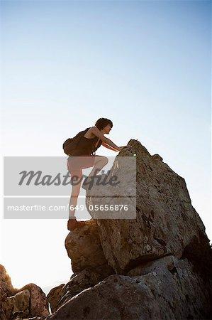 Hiker climbing rocks on hill