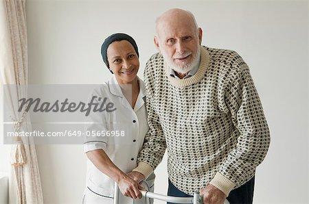 Caretaker helping older man with walker