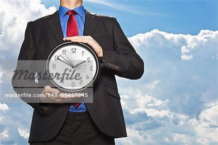 Businessman holding backwards clock