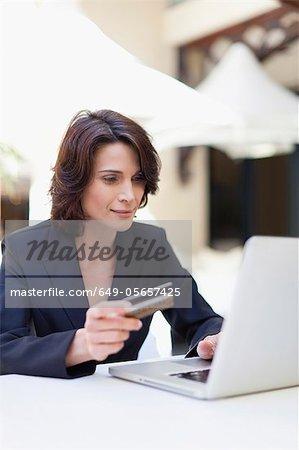 Businesswoman shopping online outdoors