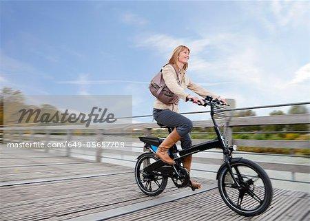 Woman riding bike on wooden walkway