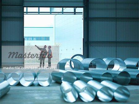Workers examining warehouse walls