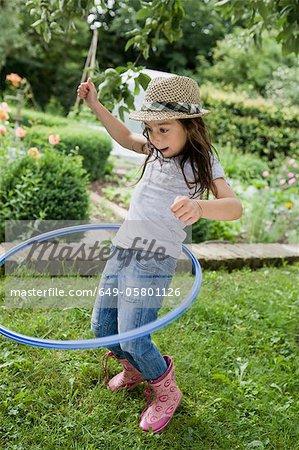Girl playing with hula hoop in backyard