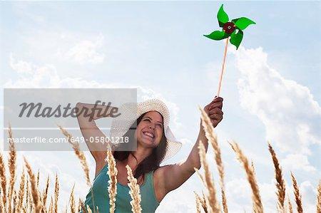 Woman holding pinwheel in wheatfield