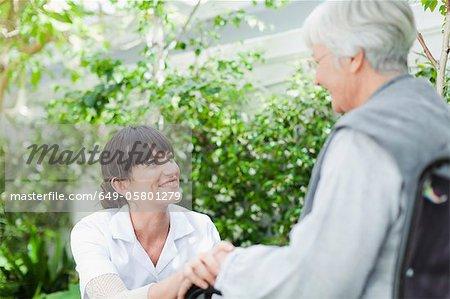 Nurse talking to older patient outdoors