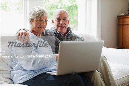 Smiling older couple using laptop