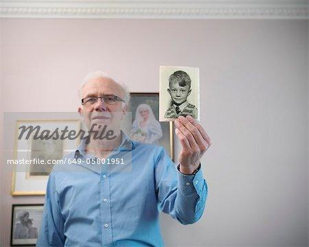 Older man holding old photograph