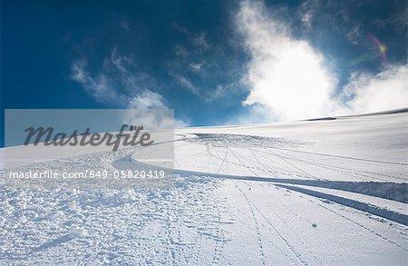 Ski and snowboard tracks on snowy hill