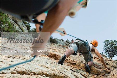 Climbers scaling steep rock face