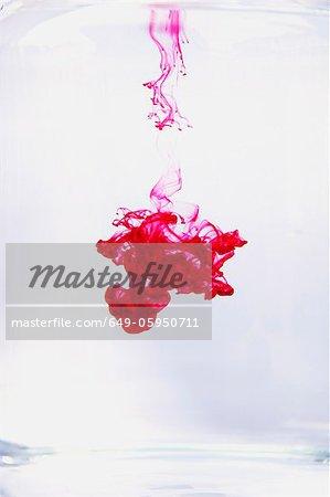 Red liquid dissolving in water