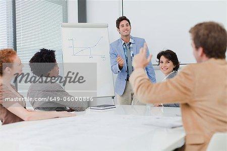 Businessman raising hand in meeting