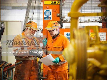 Engineer teaching apprentice in factory