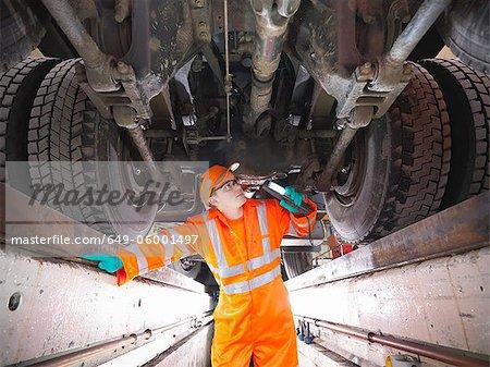 Apprentice engineer examining engine