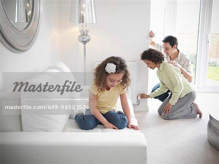 Couple adjusting radiator in living room